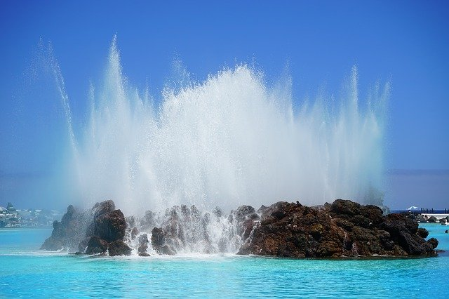 A fountain in front of a body of water