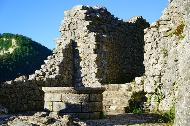 A stone building that has a rock wall